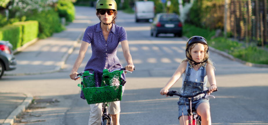 Kvinna och barn som cyklar längs en villagata. Båda har hjälm.