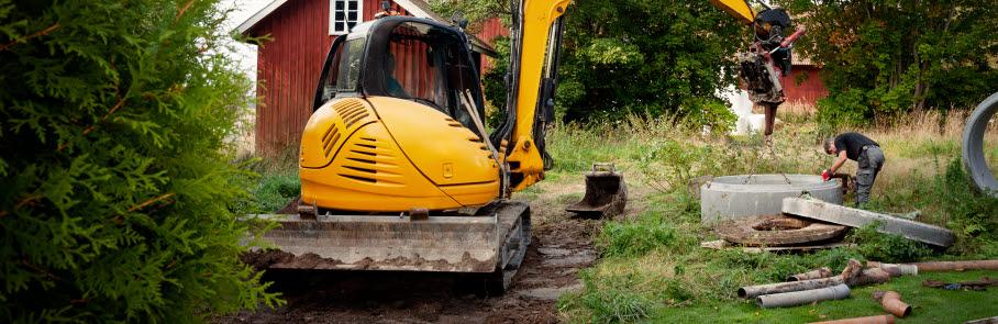 Gul grävskopa som gräver jord på tomt