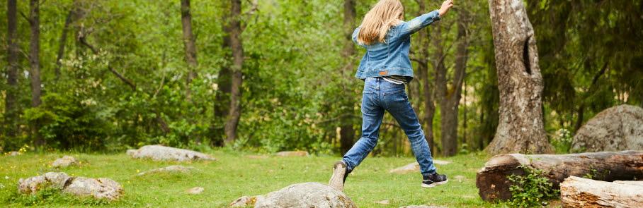Flicka hoppar från en sten till en annan i skogen