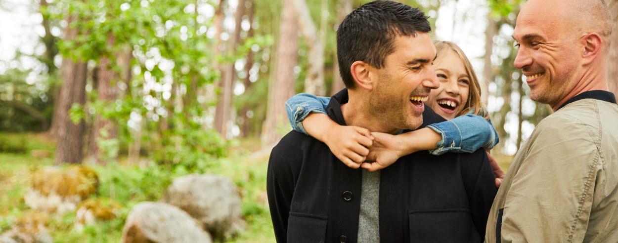 Två män står bredvid varandra i skog, den ena mannen bär en flicka på ryggen, den andra mannen håller om demalla är glada