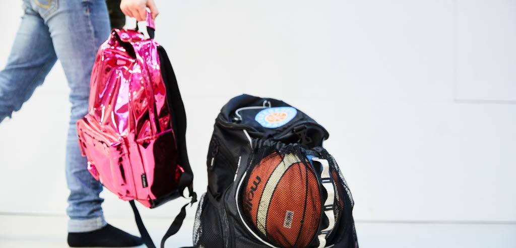 Person med blå jeans står med en rosa ryggsäck i handen, bredvid på golvet står en svart ryggsäck med en synlig basketboll i