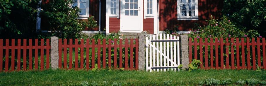 Röd stuga med vita knutar, rött staket framför.
