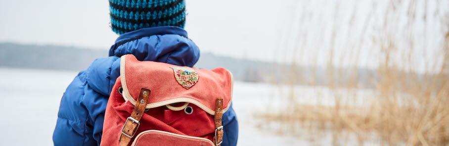 Barn med ryggsäck vid isen