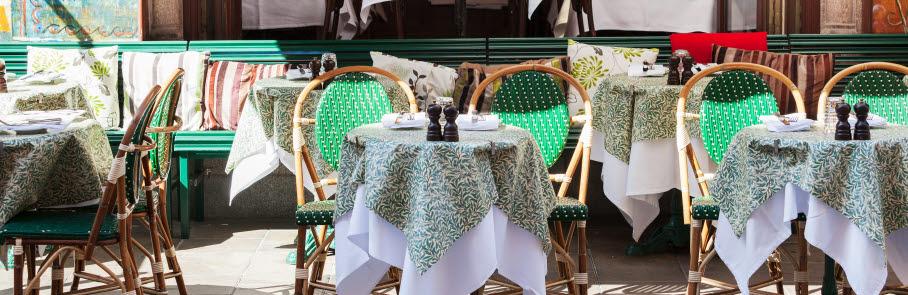 Uteservering, små runda bord med grön duk. Och två stolar vid bordet.