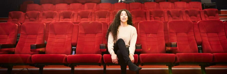 Ungdom sitter på en röd biografstol i kulturbiografen