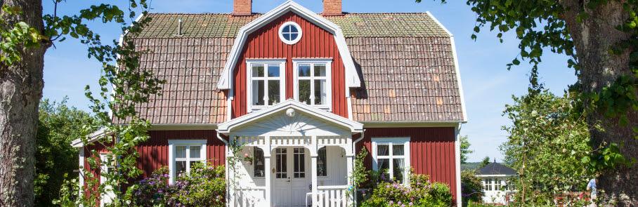 En gammal vacker, röd trävilla med vitt skärmtak över ytterdörren.