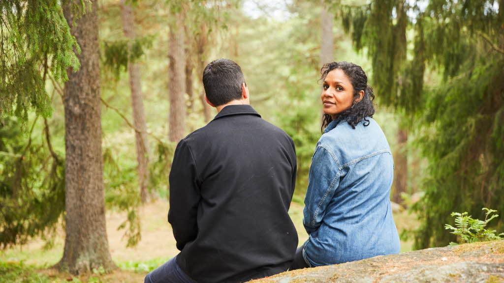 Ett par sitter på en sten i skogen