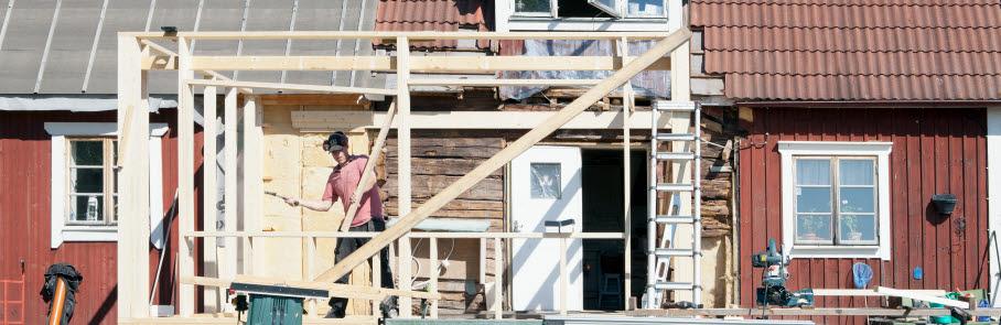Ett rött, äldre trähus med byggnadsställning för utbyggnad.