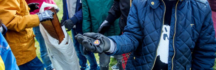 Barn som plockar skräp med vantar och påsar från Håll Sverige Rent.