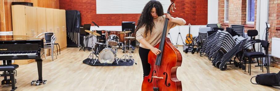 Ungdom spelar cello i ett konsertlokal