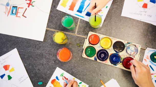 Bild ovanifrån, flera händer som målar med vattenfärg
