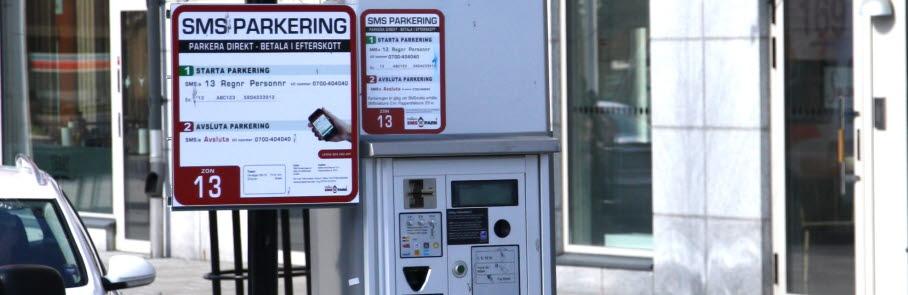 En parkeringsautomat med en skylt som instruerar hur man sms-parkerar.