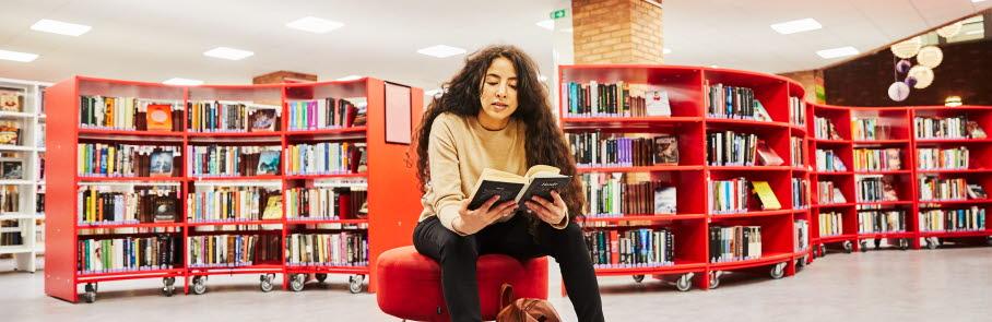 Ung kvinna läser bok på biblioteket