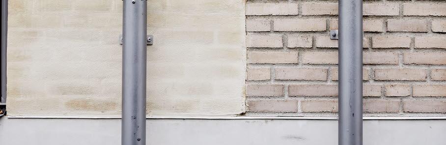 En fasad på ett flerbostadshus med stuprör