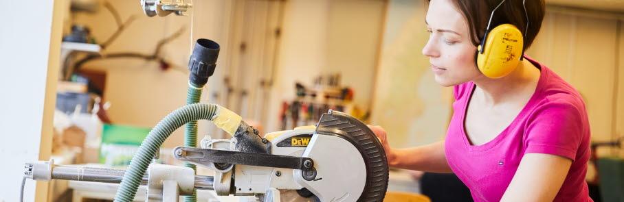 Kvinna arbetar med maskinsåg i verkstad
