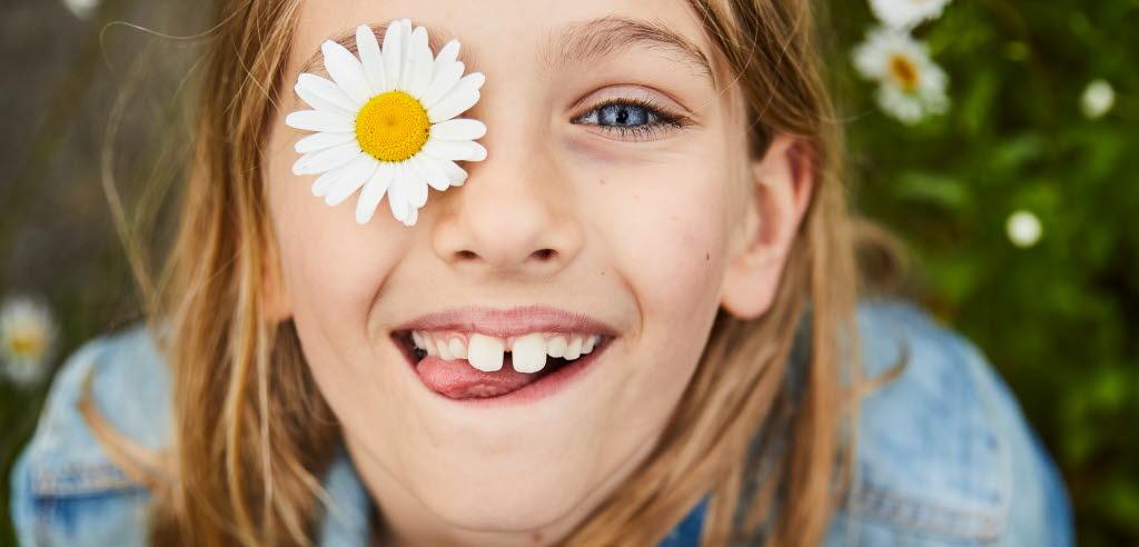 Flicka med blomma lagd över ena ögat