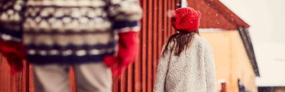 Barn framför röd vägg
