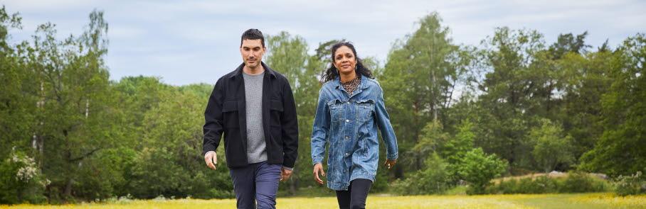 Kvinna och man går på en äng med gula blommar vid Bögs gård