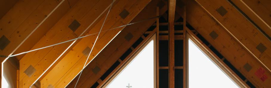 Insidan av ett hus som håller på att byggas. Huset har stora fönster och synlig trästomme.