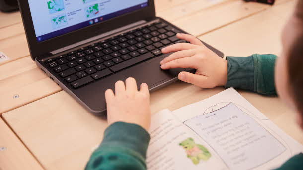 Barn med grön tröja har båda händerna på bärbar dator på bord framför sig